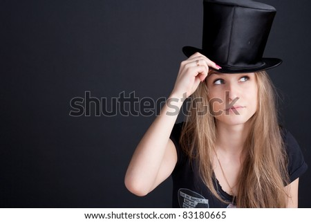 beautiful smiling girl in a black hat on a dark background - stock photo