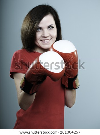 beautiful smiling girl in a red shirt and red boxing gloves on a gray background - stock photo