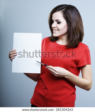 beautiful smiling girl in a red shirt holding a poster and pen in the other hand and shows him - stock photo