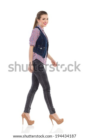 Beautiful smiling girl in jeans waistcoat walking and looking at camera. Full length studio shot isolated on white. - stock photo
