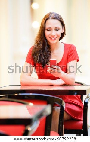 Beautiful smiling girl in red dress sits in cafe and reads sms on phone. - stock photo