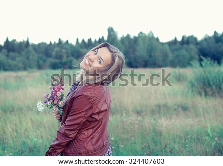 Beautiful smiling girl in the field with flower - stock photo