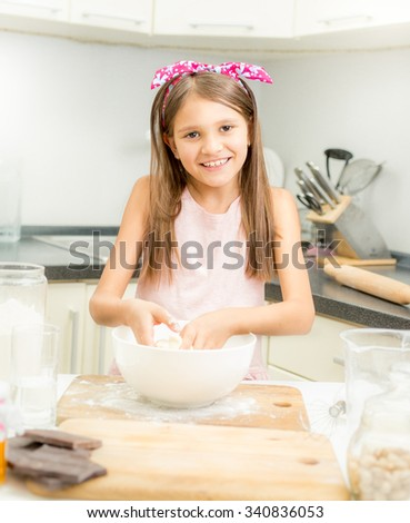 Beautiful smiling girl making dough for pie in white bowl - stock photo