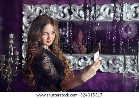 Beautiful smiling girl making selfie in luxury modern interior. Attractive female taken pictures of her self against the mirror with antique silver frame. - stock photo