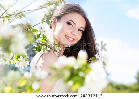 Beautiful smiling girl near blossom cherry tree with white flowers  in spring garden - stock photo