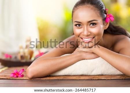 Beautiful smiling girl outdoor portrait at massage spa. Serene happy Balinese woman relaxing looking joyful at camera - stock photo