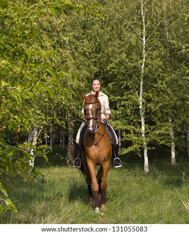 Beautiful smiling girl riding a brown horse through woodland - stock photo