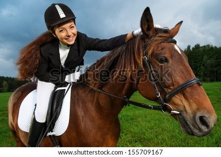 Beautiful smiling girl sitting on a horse outdoors  - stock photo