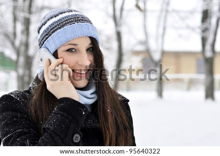 beautiful smiling girl talking on cell phone in snowy winter park - stock photo