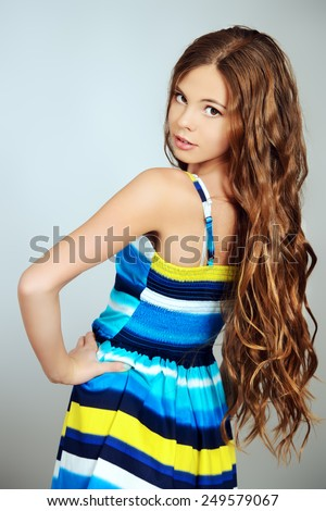 Beautiful smiling girl teenager with long curly hair posing in bright summer dress. Studio shot. - stock photo