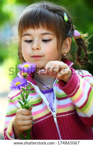Beautiful smiling girl with a flower  - stock photo