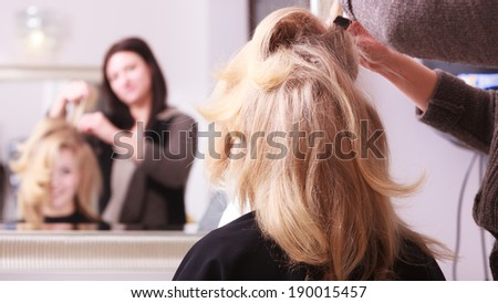 Beautiful smiling girl with blond wavy hair by hairdresser. Hairstylist combing female client young woman in hairdressing beauty salon. Hairstyle. - stock photo