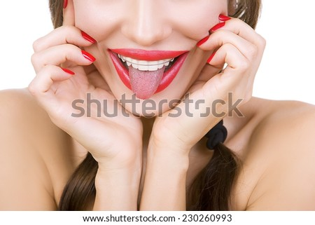 Beautiful smiling girl with retainer for teeth and with red lipstick sticking her tongue out, close-up - stock photo