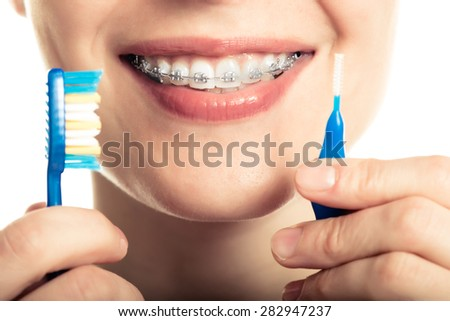 Beautiful smiling girl with retainer for teeth brushing teeth on a white background. - stock photo