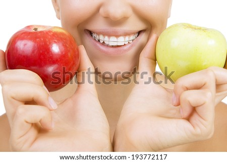 Beautiful smiling girl with retainer for teeth - healthy teeth and apples (Close Up, Isolated on white) - stock photo