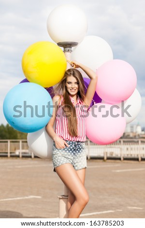 beautiful smiling lady with long silky hair in short denim shorts and sleeveless striped top leans on light-pole holding bunch of bright balloons - stock photo
