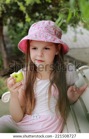 Beautiful smiling little girl sitting on a bench in panama eats an apple in a summer park outdoor - stock photo