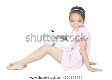 Beautiful smiling little girl with white bear toy sitting over white - stock photo