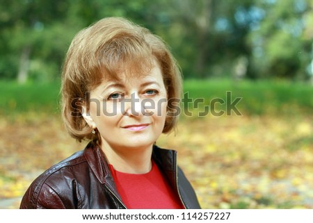 Beautiful smiling middle-aged woman outdoors in the park sitting with yellow leaves in background - stock photo