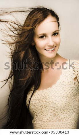Beautiful smiling natural young woman with the wind blowing through her long brunette hair - stock photo