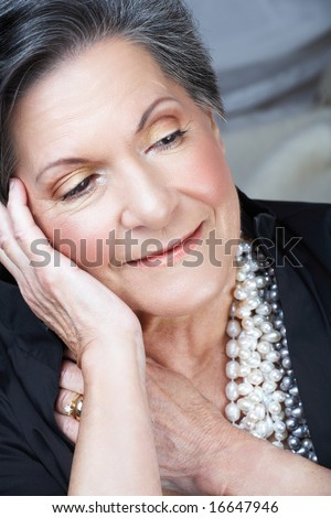 Beautiful smiling older woman with short black and grey hair and pearl necklace in her 70s - stock photo