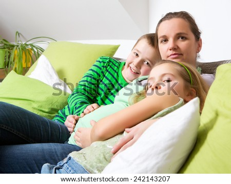 Beautiful smiling pregnant mother with her children - stock photo