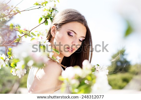 Beautiful smiling pretty teen girl near blossom cherry tree in spring garden - stock photo