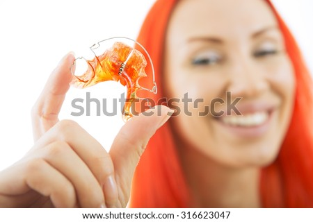 Beautiful Smiling Redhead Girl Holding red Retainer, Braces for Teeth. Orthodontics Dental Theme, Methods of Teeth (Bite) Correction, Close-up - stock photo