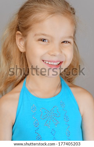 Beautiful smiling schoolgirl in blue dress, on gray background. - stock photo