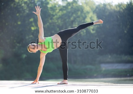 Beautiful smiling sporty fit blond young woman in green sportswear working out outdoors on wooden pontoon on the lake, standing in ardha chandrasana, half moon posture, full length - stock photo