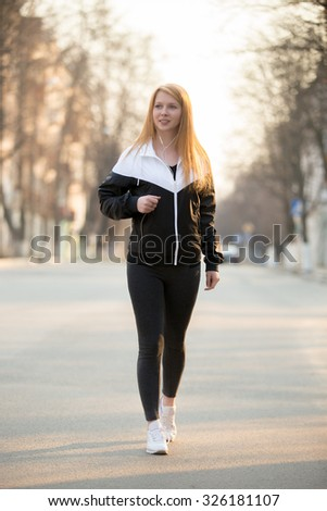 Beautiful smiling sporty girl in earphones walking in the morning street - stock photo