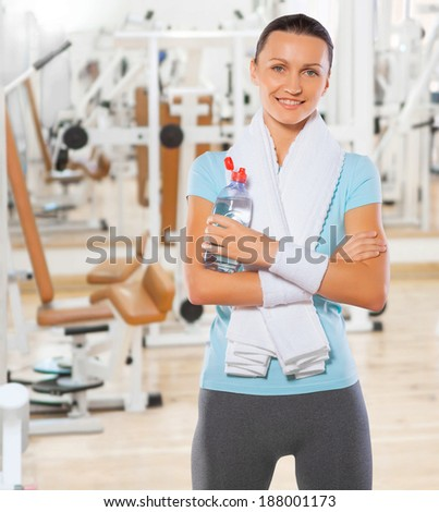 beautiful smiling standing sportswoman with bottle of water in gym - stock photo