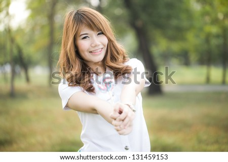 Beautiful smiling teenage girl giving candy to you - stock photo