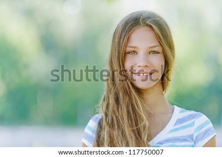 Beautiful smiling teenage girl in blue blouse, against green of summer park. - stock photo