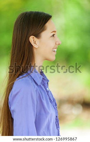 Beautiful smiling teenage girl in blue shirt profile, against background of summer green park. - stock photo