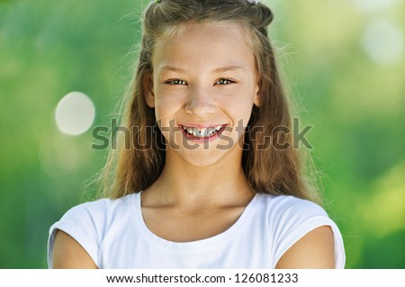 Beautiful smiling teenage girl in white blouse, against green of summer park. - stock photo