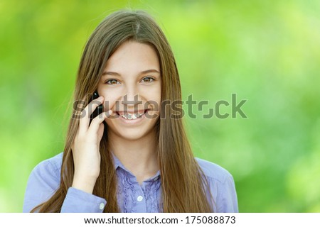Beautiful smiling teenage girl in white dress talking on mobile phone, against background of summer green park. - stock photo