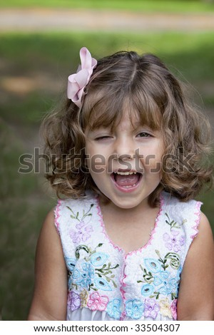 Beautiful smiling winking little three-year-old girl with bouncy natural curly hair held back with a pink bow. - stock photo