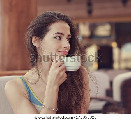 Beautiful smiling woman drinking coffee from cup and looking - stock photo