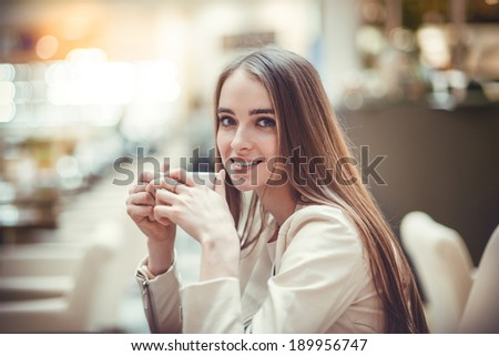 Beautiful smiling woman drinking coffee in cafe - stock photo