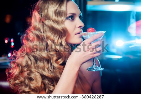 Beautiful smiling woman drinking martini at the bar - stock photo