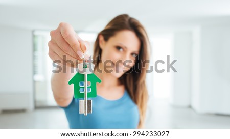 Beautiful smiling woman holding house keys of her new house, real estate and relocation concept - stock photo