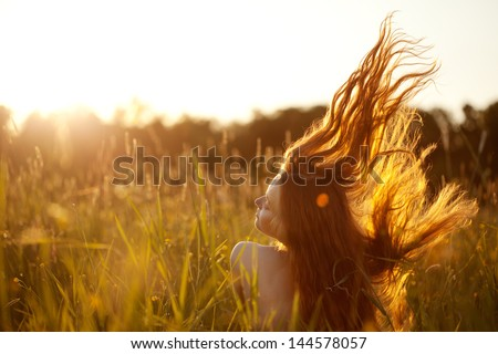 Beautiful smiling woman in a field at sunset - stock photo