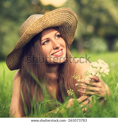 beautiful smiling woman in a hat lying on the grass in a summer park with a bouquet of white flowers - stock photo