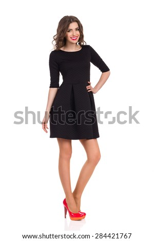 Beautiful smiling woman in black mini dress standing and holding hand on hip. Full length studio shot isolated on white. - stock photo