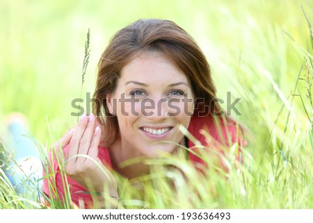 Beautiful smiling woman laying in country field - stock photo