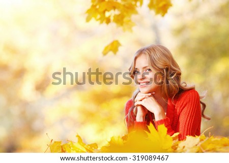 Beautiful smiling woman lying in autumn maple leaves in park - stock photo
