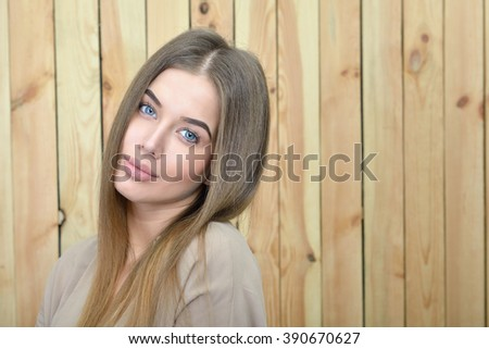 Beautiful smiling woman over woodwn background - stock photo