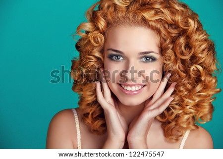 Beautiful smiling woman portrait with long glossy hair over blue - stock photo