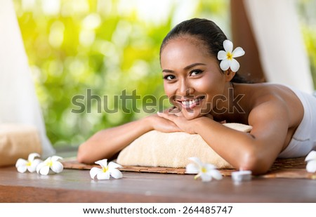 Beautiful smiling woman relaxing under canopies for massage - stock photo